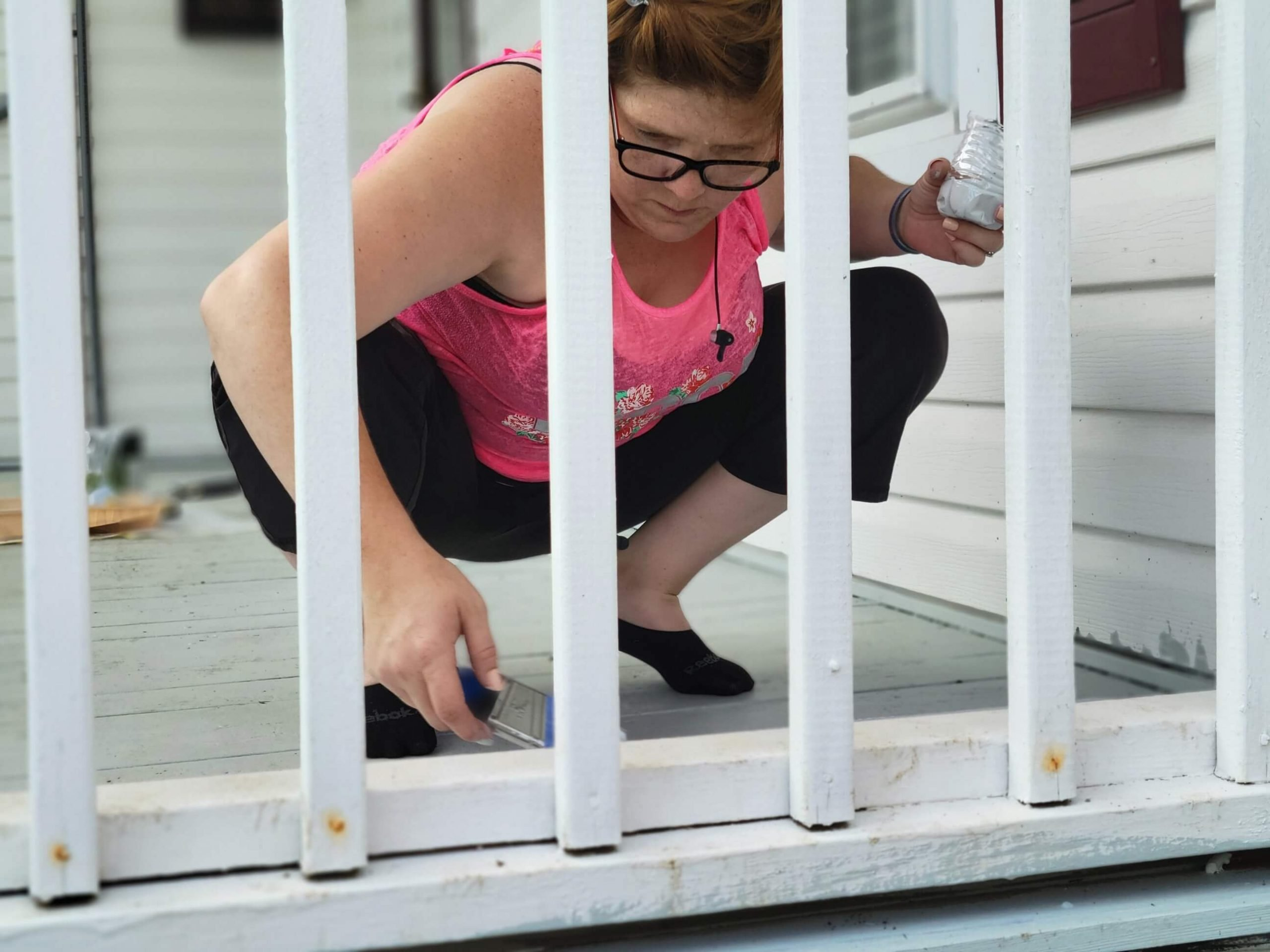Andrea paints a porch for a family in need of home repairs.